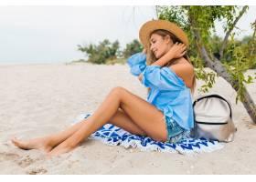 时髦漂亮的微笑着的女人坐在沙滩上瘦腿_1027376601