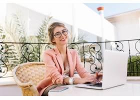 时髦的年轻女子微笑着在笔记本电脑上工作_1021602301