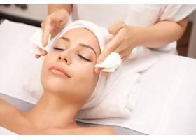 有魅力的女人在水疗沙龙做面部美容手术_563369601
