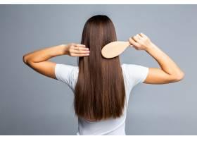 梳理健康直长女性头发的后视图孤立在灰色_847345601