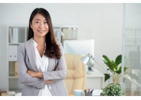 欢快的韩国女商人交叉双臂在办公室摆姿势_583952601