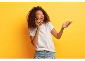 欣喜若狂的卷发女子喜欢通过手机进行有趣的_1249484001
