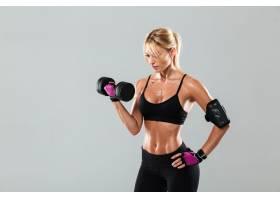 年轻专注的女运动员拿着哑铃做运动_779154301