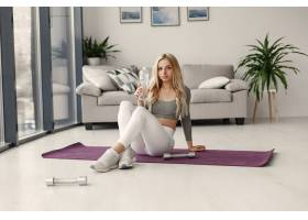 家里的女孩女人做瑜伽拿着哑铃和水的女_1175679101