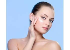 年轻女子把面霜涂在蓝色的脸上_1062552101