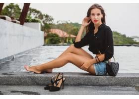 年轻性感美女赤脚坐在游泳池边长而瘦的棕_1052294501