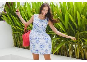 年轻时髦的美女穿着蓝色印花连衣裙红色的_1052239601