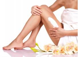 一位身材美丽的女子在白色背景下在腿上涂了_1191656601