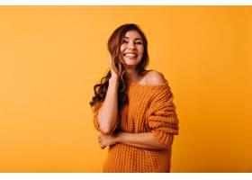 一位身着橙色服装的可爱女人抚摸着她的棕色_1193503401