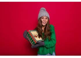一位长发年轻女子穿着绿色毛衣戴着灰色_1135583901