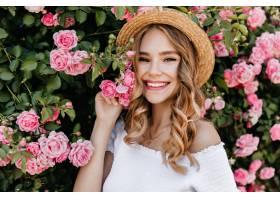一头卷曲的金发可爱的女孩在花园里摆姿势_1157842501