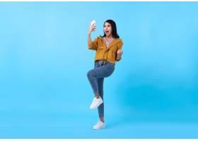 一幅快乐的亚洲年轻女子的肖像在蓝色背景_924329601