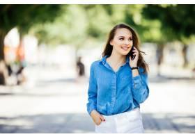 时尚性感的女人在城市街头边走边说手机_1061141701