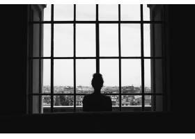 一位孤独的女性站在窗户前看着建筑物的黑白_1194262201