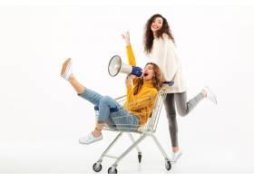 两个穿着毛衣的快乐女孩在白色墙上玩购物车_673016901
