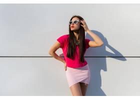 穿着夏装戴着墨镜的时髦女人在白色的城市_1187688701