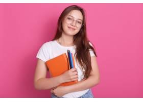 可爱的年轻女子手持课本和彩色铅笔的特写肖_898834101