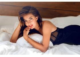 穿着黑色内衣的年轻性感女子在床上摆姿势_968700501