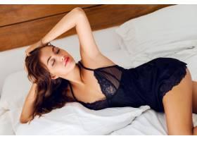 穿着黑色内衣的年轻性感女子在床上摆姿势_968701701