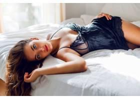 穿着黑色内衣的年轻性感女子在床上摆姿势_968702001