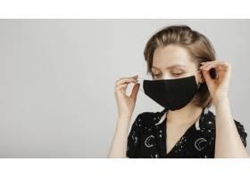穿着黑色衬衫戴着面具的女人_1247646401