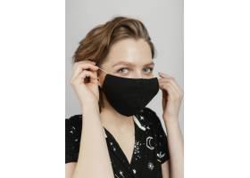 穿着黑色衬衫戴着面具的女人_1247646501