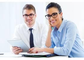 商务人士使用数字平板电脑在办公室工作_123291201