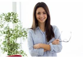 商务年轻女子在办公室里看着摄像机_123286701