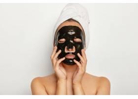 近距离拍摄的严肃年轻女子戴着黑色面膜闭_1249521501