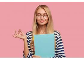 高兴的金发大学生在粉色墙上摆姿势_1114093601