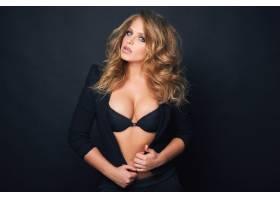 黑色背景下美麗的金發性感女子肖像_907005201