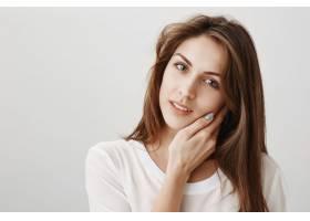 温柔美丽的女人抚摸着柔软的皮肤凝视着_979990601