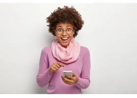 漂亮的女性头发清爽指着手机设备戴着_1249516001