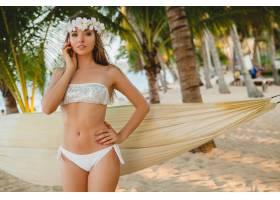 穿着白色比基尼泳衣的年轻性感女子在热带海_1151409801