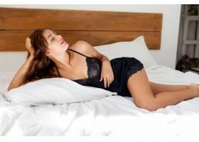 穿着黑色内衣的年轻性感女子在床上摆姿势_968701301
