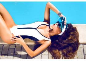 穿着黑色比基尼的性感美女在游泳池边放松的_1205744801