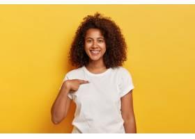 笑容满面的黑皮肤女孩指着自己穿着白色T_1193246401
