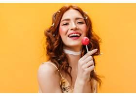 红色卷发的女人笑着吃着棒棒糖橙色背景下_1267781201