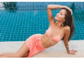 年轻的亚洲性感美女穿着粉色比基尼躺在_1108306701