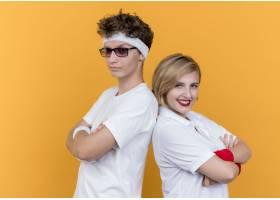 年轻的运动情缺少罡�L侣男女背靠背站在橙色的墙上_1260975801
