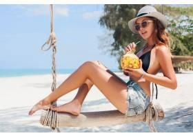 度假的年轻性感美女坐在海边秋千上热带海_1108300901