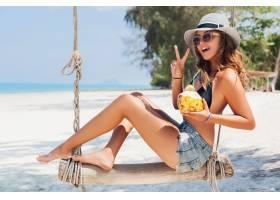 度假的年轻性感美女坐在海边秋千上热带海_1108301101