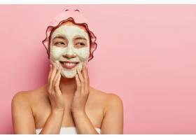 快乐的年轻女子戴着粘土面膜在美容院做水_1249582501