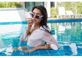 性感的女人带着波西米亚配饰在游泳池摆姿势_1135982701