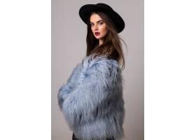 亮灰色墙上挂着蓬松的蓝色外套和黑色帽子的_1187689701