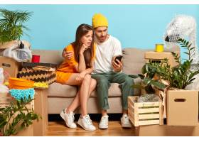 困惑的女人和男人看着智能手机设备搬到新_1249441801