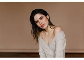 在棕色墙上摆姿势的快乐的年轻女子可爱的_1260822901
