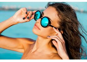 在阳光明媚的海滩上蓝色海水中戴着眼镜_936176401