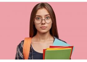 可爱的学生戴着眼镜在粉色墙上摆姿势_1113970901