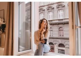 可爱的年轻女子穿着时髦的牛仔裤在家里喝_1090672501